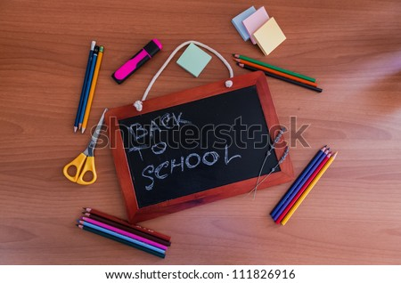 Small slate blackboard with the words Back to School surrounded by pencils, crayons, scissors and stationery