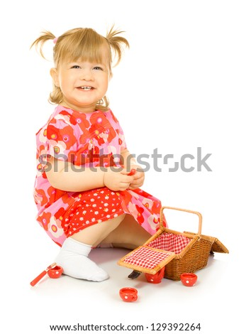 Small smiling baby in red dress with toy basket