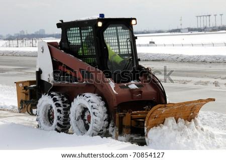 Small snowplow plowing sidewalk after heavy snowfall