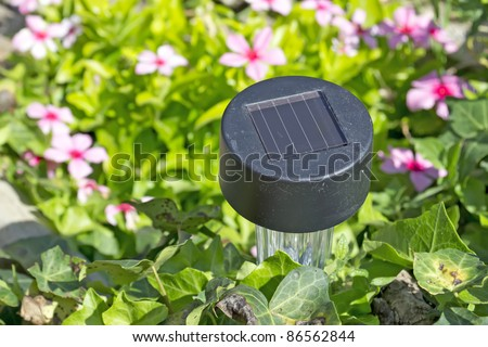 small solar garden light in a flower bed with stones - stock photo