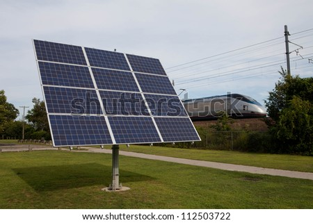 Small solar panel next to train tracks promoting green energy