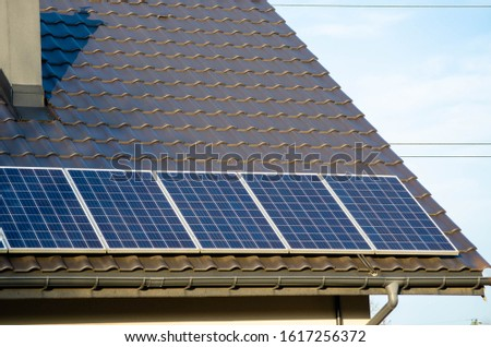 Small solar panels installation on roof. Blue photovoltaic solar panels installation on a house during sunny day.