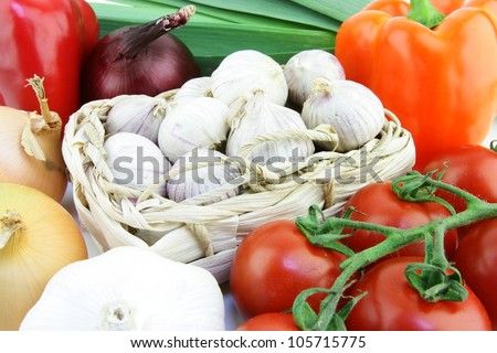 Small solo garlic bulbs in a woven basket with vegetables around it.