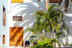 Small spanish patio with palm trees and banch. Old wooden door and windows in Garachico, Tenerife, Spain