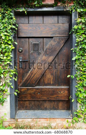 Small Spanish style dark stained wood door to secret garden with grated window