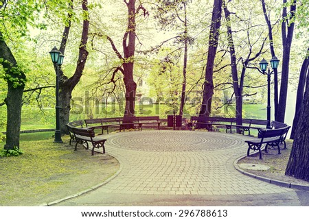 Small square and garden benches in central park of riga city by springtime, Latvia. Image slightly toned for inspiration of retro style