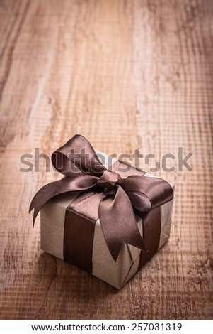 small square vintage gift box with brown bow on old wooden board with copyspace holiday concept