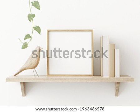 Small square wooden frame mockup in scandi style interior with trailing green plant, bird, pile of books and shelf on empty neutral white wall background. 3d rendering, illustration