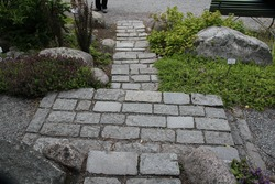 Small stairs stacked with stone in front of  narrow pathway in a park.