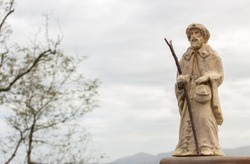 Small statue of Saint James on Camino de Santiago. Pilgrimage concept. Main christian saint of pilgrims. Ancient sculpture of Saint James in Pyrenees mountains, France. Religious architecture.