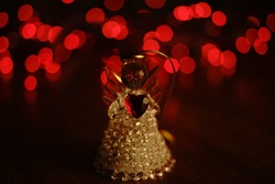 small statuette of an angel on a table against a background of red lights.