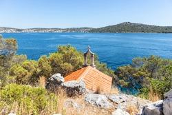 Small stone sanctuary, chapel on the stone rock, above beautiful, blue adriatic sea at the Rogoznica, Croatia