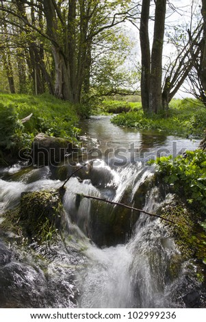 Small stream with water cascade flowing through idyllic landscape (slow shutter), Denmark