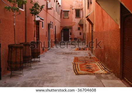 Small street in Marrakech's medina (old town). In Marrakech the houses are traditionally pink. Morocco. - stock photo