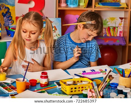 Small students girl and boy painting in art school class. Child drawing by watercolor paints on table in kindergarten. Boy is holding a brush behind his ear.