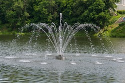 small summer fountain on the pond of a provincial town