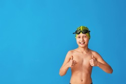small swimmer in a swimming cap, glasses and a bathing suit on a blue background. the child shows thumbs up, sign of approval, advertising. boy is studying at a sports swimming school. Copy space