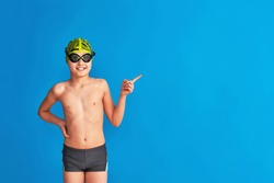 small swimmer wearing a swimming cap, glasses and a bathing suit on a blue background. child points his finger to the side, advertising. boy is studying at sports school, learning to swim. Copy space