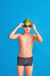 small swimmer wearing swimming cap, glasses and bathing suit on blue background. child adjusts his glasses, water go. boy is studying at sports school, learning to swim. Problems with swimming goggles