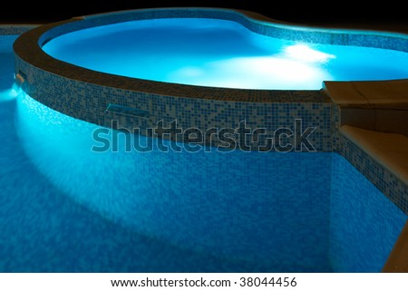 Small swimming pool with blue water and lights at night