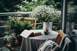 Small table, book and flowers on a beautiful terrace or balcony