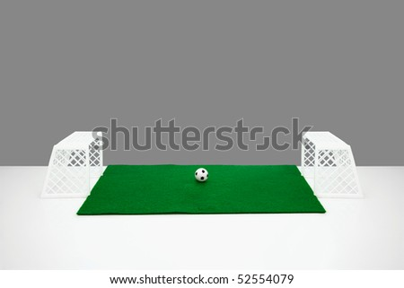 small table top football goal posts. football and green felt fake football pitch on the edge of a white table