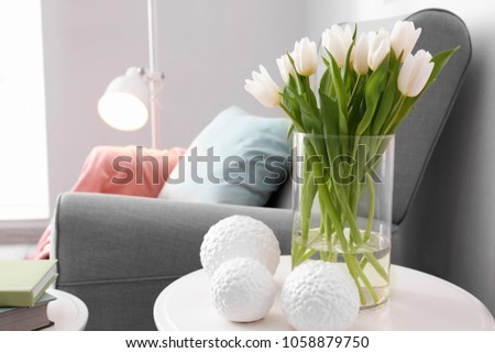 Small table with bouquet of tulips and decor in living room #1058879750