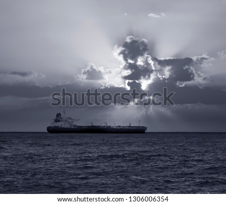 Small tanker anchored off the coast at the sunset. Converted black and white. Toned blue.