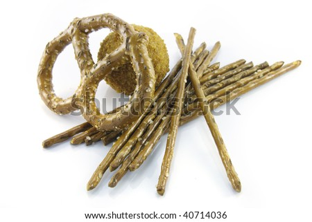Small tasty scotch egg with salty pretzel sticks and single pretzel  on a reflective white background