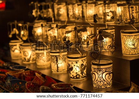 small tea lights in decorated glasses at a christmas market close up