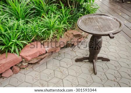 Small teak wooden circle table in green garden