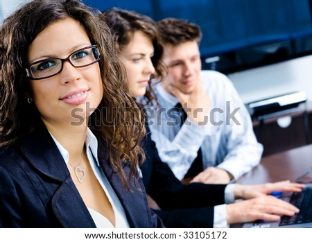 Small team of young happy businesspeople working together at meeting room at office. Huge plasma TV screen in background.