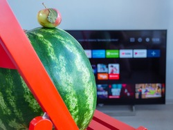 Small tiny red apple on the top of a big watermelon sit on a red wooden table and watch TV. Opposites attract concept.