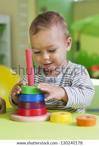 Small toddler or a baby child playing with puzzle circle shapes on a low table in a colorful children room in a nursery or preschool.