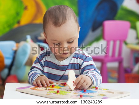 Small toddler or a baby child playing with puzzle shapes on a low table in a colorful children room in a nursery or preschool.