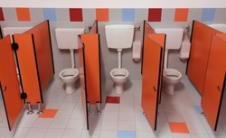 small toilet with red door in the school without children