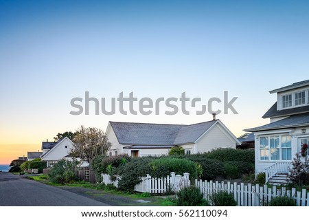 Small town America houses with white picket fences in sunrise light. Background for old fashioned nostalgic American town concept. Morning in America. Copy space #562110094