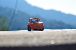 small toy car jeep placed on wall with some sun light and mountains in background