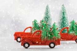 Small toy cars carring christmas tree on blue background with snow. Seasonal holidays, greeting card, christmas mood concept. copy space close up