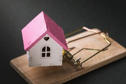 Small toy house in a mousetrap. Concept on the topic of housing traps and fraudulent real estate transactions