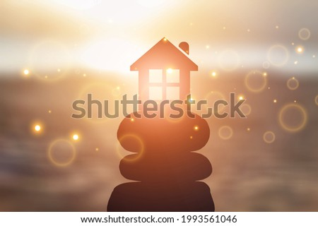 Small toy house on sea beach at sunset, family travel and summer vacation