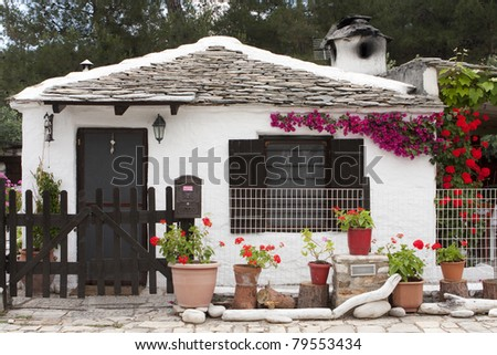 Small traditional greek house in white color and green plants