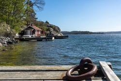 Small traditional red house on the water. Pier berth in bay next to the residence for anchoring the yacht. Wooden jetty in the foreground with a metal ring eyelets for mooring securing the yacht boat.