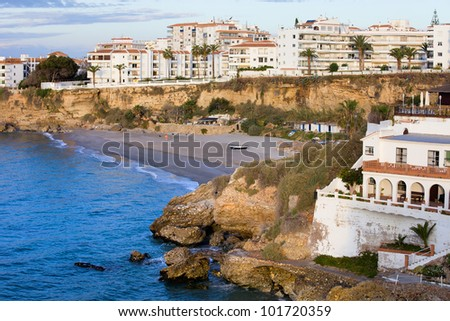 Small tranquil beach surrounded by cliffs and apartment buildings in scenic resort town of Nerja at Costa del Sol, Andalucia, Spain.