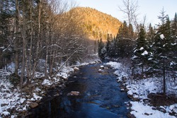 Small tributary flowing in the Jacques-Cartier National Park seen during a late Fall blue hour morning, with a golden mountain in the background, Stoneham-et-Tewkesbury, Quebec, Canada