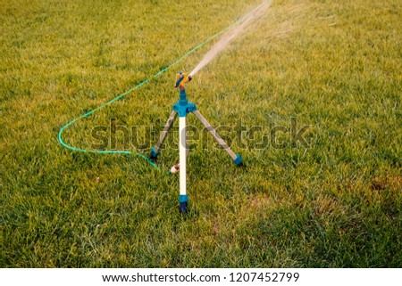 Small tripod sprinkler watering on lawn #1207452799