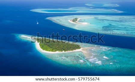 Stock Photo Small tropical island in Maldives atoll from aerial view