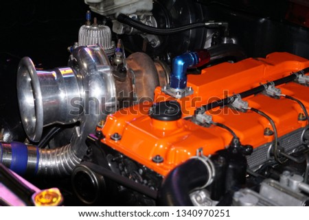 Small truck engine with a orange cover is somewhat blur, Engine that is customized to enter the car contest in the motor show, Motor show background. #1340970251