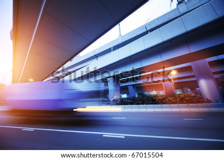 Small truck speeding under industrial bridges. Long exposure, burred motion.