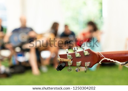 Small tuner on headstock of acoustic guitar on background of blurred people on sunny day - Shutterstock ID 1250304202